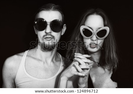 Studio portrait of a young couple wearing sunglasses on a black background