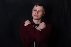 Studio portrait of a young man in a red sweatshirt against black background. A deaf-mute guy shows a