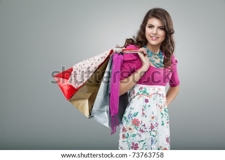 studio portrait of a young woman in a colourful outfit, holding in one hand three shopping bags. she is laughing and looking very happy.