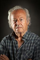 Studio portrait of an aged powerful, rugged man. Black backround