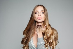 Studio portrait of an attractive blond woman with long thick hair and professional make-up wearing an elegant silver blouse, an air kiss on the camera on a gray background. Isolate. The concept of bea