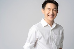 studio portrait of an attractive young asian businessman white shirt half body isolated on grey background