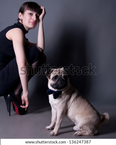 Studio portrait of an elegant pug dog gentleman wearing blue bow and sitting on the floor, with his owner beautiful young woman model sitting behind. Gray background