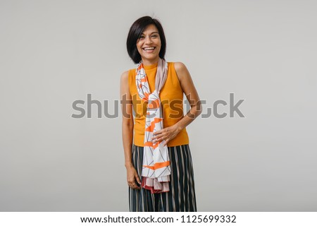 Studio portrait of an older and attractive Chinese Asian woman against a white backdrop. She is smiling and is wearing an orange sweater, a dark dress and has a scarf draped over her neck.