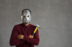 Studio portrait of an unknown man on a gray background who is dressed in a spooky maniac mask. Terrible dark-skinned man with a hammer in his hands and an iron mask on his face. Identity concealment