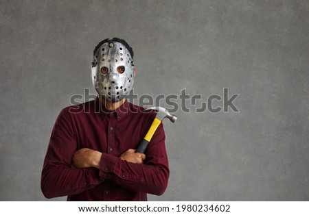 Studio portrait of an unknown man on a gray background who is dressed in a spooky maniac mask. Terrible dark-skinned man with a hammer in his hands and an iron mask on his face. Identity concealment Сток-фото ©