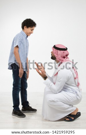 Studio portrait of arab father and son