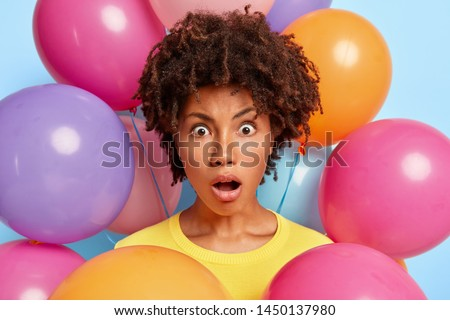 Studio portrait of astonished beautiful woman stares at camera, keeps jaw dropped, reacts on birthday present, poses near helium balloons, being very emotional. People human emotions and special event #1450137980