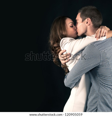 Studio portrait of attractive young couple on black background with copy space.