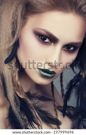 Studio portrait of attractive young woman with creative bright makeup and hairstyle with black feathers