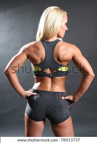 Studio portrait of back side of professional female fitness model.