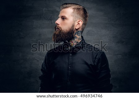 Studio portrait of bearded hipster male with tattoo on his neck.