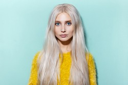 Studio portrait of beautiful blonde girl with blue eyes wearing yellow sweater on cyan, aqua menthe color.