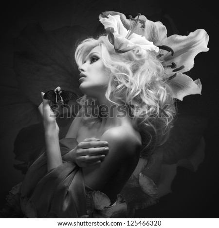 studio portrait of beautiful blonde wearing flowers in her hair and tropical butterfly sitting on her hand on dark background