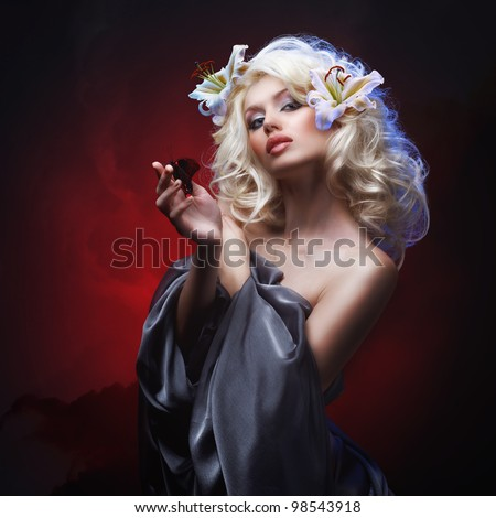 studio portrait of beautiful blonde with blue eyes in gray cloth wearing flowers in her hair and tropical butterfly sitting on her hand on dark red abstract background