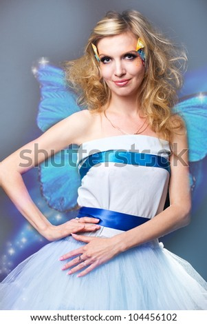 studio portrait of beautiful blonde with blue eyes with butterfly in her hair