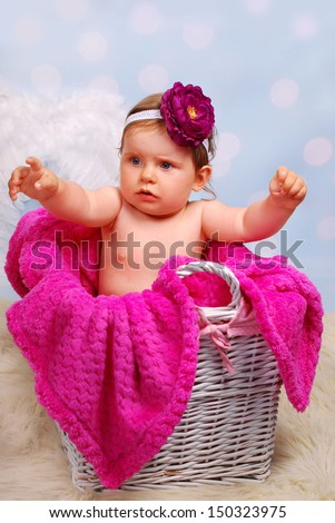 studio portrait of beautiful 10 months baby girl sitting in white wicker basket