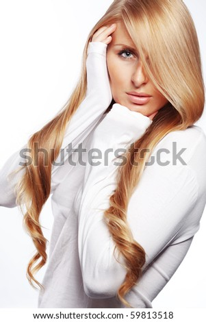 Studio portrait of beautiful young woman with long gold hair