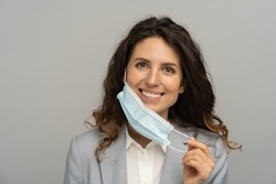 Studio portrait of business woman taking off mask over grey background. Female removing medical mask from face and looking at camera. Coronavirus, Covid-19 ended. Pandemic is over concept.