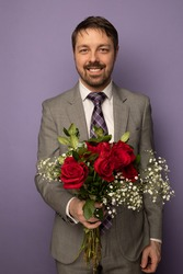 Studio portrait of  caucasian man holding a dozen of roses and smiling. He is wearing a suit and tie and the background is purple.