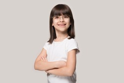 Studio portrait of confident happy brown-haired 6 years old cute girl wearing eyeglasses, standing with folded hands, isolated on grey background. Smiling smart little cutie looking at camera.