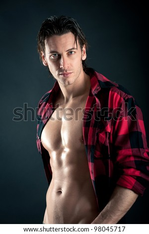 Studio portrait of confident young man with plaid shirt against dark background.