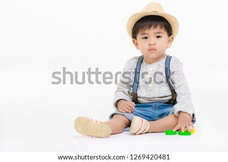 Studio portrait of cute, adorable, Asian toddler boy wearing denim overalls, straw hat, long sleeve T-shirt, sitting on floor, playing toys, look at camera on isolated white background