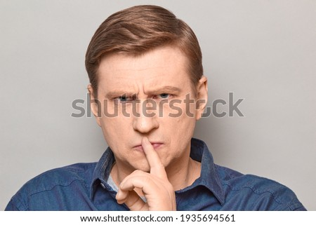 Studio portrait of disgruntled strict blond mature man showing silence gesture with finger over lips, requiring to stop talking and keep mouth shut, with frowning face. Headshot over gray background ストックフォト ©