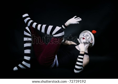 Studio portrait of Dramatic funny mime in white hat with red flower and striped gloves lying on floor on black background