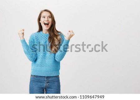 Studio portrait of excited european girl overwhelmed with emotions, raising fists in victory, shouting and looking up, feeling upbeat while standing over gray background. It is time for lunch, finally