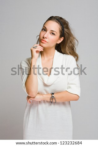 Studio portrait of friendly pensive young brunette beauty.