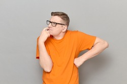 Studio portrait of funny focused puzzled blond mature man with glasses, wearing T-shirt, touching lips with finger, thinking hard, trying to understand something, standing over gray background
