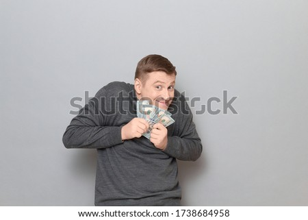 Studio portrait of funny happy mature man wearing casual jumper, holding bunch of US dollars in hands, clasping money to his chest, looking greedy and sly, standing hunched over gray background Foto stock ©