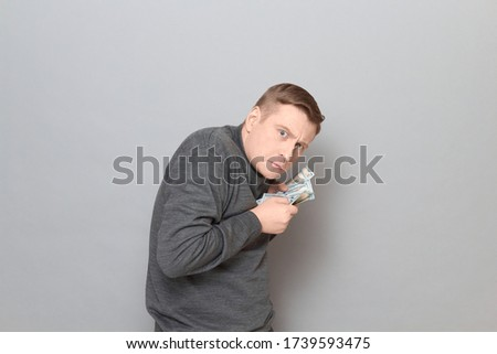 Studio portrait of funny worried mature man wearing jumper, holding bunch of US dollars in hands, clasping money to his chest, looking greedy and incredulous, standing hunched over gray background Foto stock ©