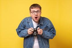 Studio portrait of goofy young man holding photocamera taking photo. Yellow background.
