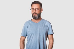 Studio portrait of handsome middleaged man looking directly at camera, having serious facial expression, malewearing casual clothing and rounded optical glasses, posing isolated over white background.