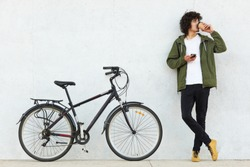 Studio portrait of handsome young Caucasian male with curly hair and little beard, drinking coffee and browsing internet using his smertphone, looking aside, standing at white wall near bicycle.