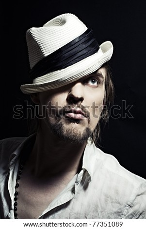 studio portrait of handsome young man in  white hat on black background closeup