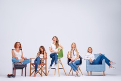 Studio portrait of happy five pretty young women sitting on chairs. White background.