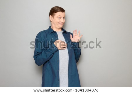 Studio portrait of happy funny blond mature man wearing blue shirt, raising hand, waving palm, saying hello or goodbye, smiling joyfully, looking friendly and goofy, standing over gray background Foto stock ©