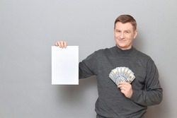 Studio portrait of happy proud mature man wearing jumper, smiling and holding bunch of US dollars and white blank paper sheet with place for your text or design, standing over gray background