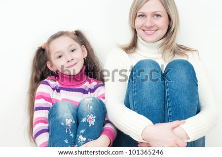 Studio portrait of happy young mother and her little daughter