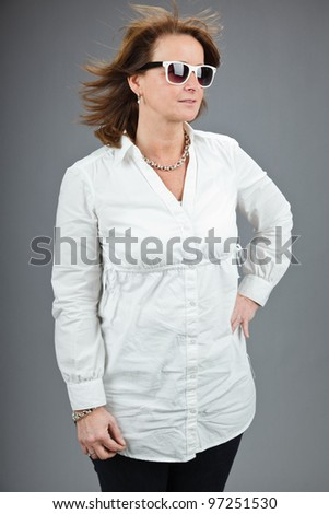 Studio portrait of middle aged woman with sunglasses and white shirt isolated on grey background