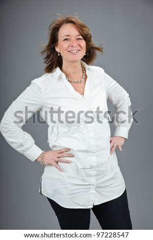 Studio portrait of middle aged woman with white shirt isolated on grey background