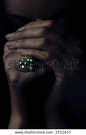 Studio portrait of model's hands with jewel ring in dramatic light - stock photo