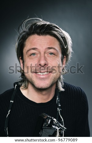 Studio portrait of photographer with expressive face and long blond hair wearing black sweater isolated on grey background.