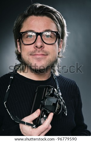 Studio portrait of photographer with expressive face and long blond hair wearing black sweater isolated on grey background. Wearing retro glasses.