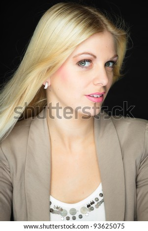 Studio portrait of pretty young woman with long blond hair isolated on black background. Wearing light brown jacket and white shirt.