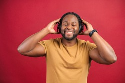 Studio portrait of relaxed cheerful African American man wearing and holding wireless headphones isolated on red wall, enjoying listening to favorite music soundtrack, wellbeing, meditation concept