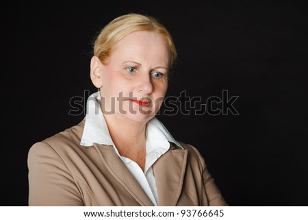 Studio portrait of senior business woman wearing light brown suit and white shirt isolated on black background.